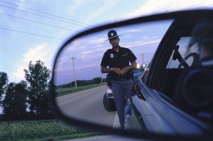DUI Traffic Stop - Priest Criminal Defense - Lawyer Vancouver Washington - picture of a cop in rearview mirror